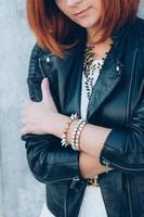 chica pelirroja con una chaqueta negra y gafas azules foto