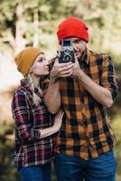 Bald guy with a beard and a blonde girl in bright hats are taking pictures with an old camera photo