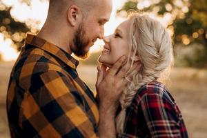 Cheerful guy with a board and a blonde girl for a walk in plaid shirts photo