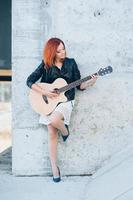 young girl with red hair with an acoustic guitar photo