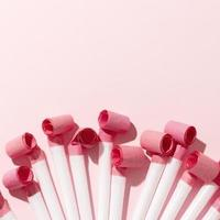Party whistles on pink background photo