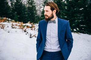 groom in a blue suit in the mountains Carpathians photo