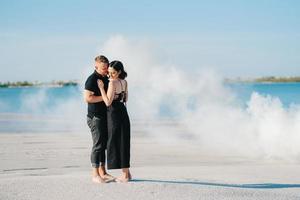 chico y una chica vestidos de negro se abrazan dentro de un humo foto