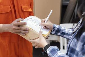 Person signing for parcel delivery photo