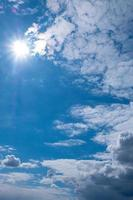 beautiful blue sky with sun, clouds and copy space vertical cropping photo