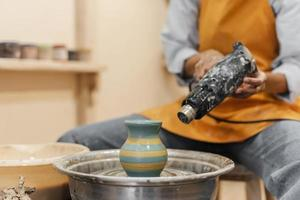 Person drying paint on pottery photo