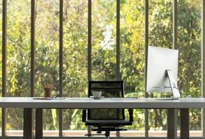 A large table with a computer of CEO and nature background photo