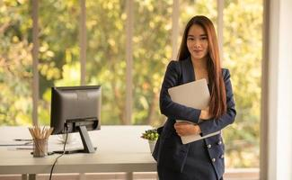 Asian business woman holding laptop photo