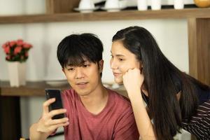 una joven pareja asiática está comiendo juntos y sonriendo felizmente mientras cocina su ensalada en la cocina. foto