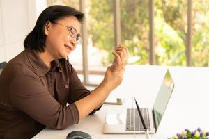 Asian business woman holding her wrist pain from working and using computer. Office syndrome photo