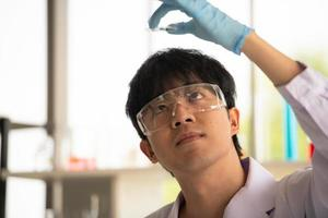 Asian young scientist lab testing and analysis chemical at the laboratory photo