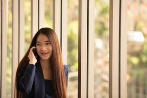 Asian business woman using mobile phone in an office photo