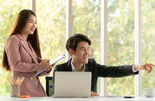 Young Asian businessman and businesswoman work in an office setting with natural background photo