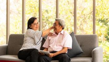 Senior hombre y mujer asiáticos se relajan de vacaciones en el fondo natural de la sala de estar con tecnología moderna foto