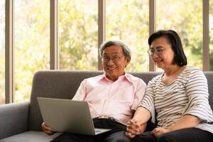Senior Asian man and woman relax on holiday in the natural living room background with modern technology photo