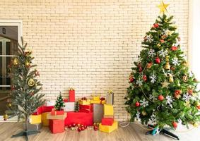 Christmas tree decorated in the living room to prepare for the new year. Decorate the living room and christmas tree with a box of red balls, golden balls, golden bells, snow stars, socks. photo