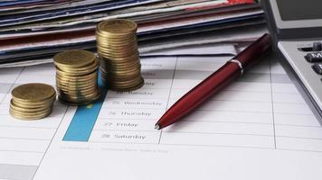 money coins stack and red pen for due date payment concept background photo