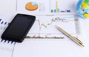 Smartphone and pen on stock infomation chart for finance concept photo
