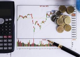Fountain pen and calculator and coins stack on Stock index chart for finance concept photo
