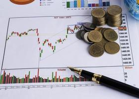 Fountain pen and coins stack on stock index chart for finance concept photo