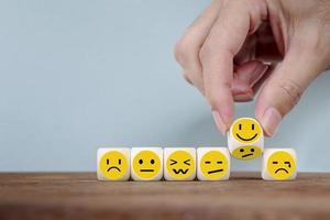 Cambio de mano con iconos de emoticonos de sonrisa cara en cubo de madera, mano volteando infeliz girando al símbolo feliz foto