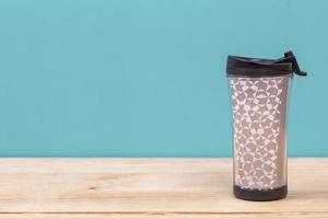 plastic tumbler glasses or thermos travel cup  isolated on wooden background photo