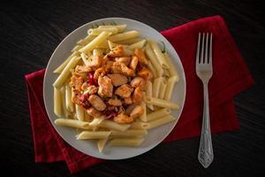 pasta penne con pollo y verduras en salsa de tomate foto