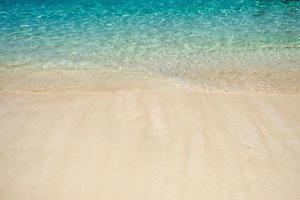 Wave of aqua sea on white sand photo