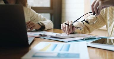 Reunión de asesores de negocios asiáticos para analizar y discutir la situación en el informe financiero en la sala de reuniones.Consultor de inversiones, asesor financiero y concepto de contabilidad. foto
