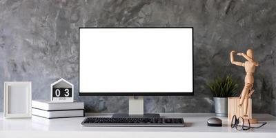Computadora de escritorio con pantalla en blanco en una habitación de oficina mínima con decoraciones y espacio de copia foto