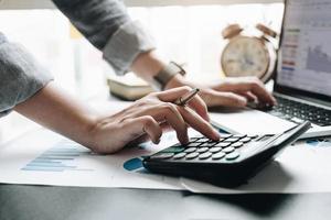 Cerca de la mano del empresario o contador que sostiene la pluma trabajando en la calculadora para calcular datos comerciales, documentos contables y computadora portátil en la oficina, concepto de negocio foto