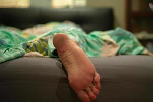Closeup of dirty feet of a man sleeping on a bed in a bedroom after working hard all-day photo