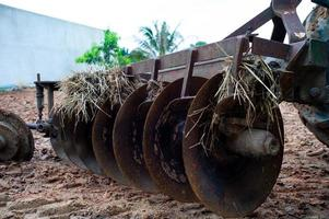 Close up of disk harrows on the back of a tractor. Dirty steel blades of a tractor with dried straw and soil photo