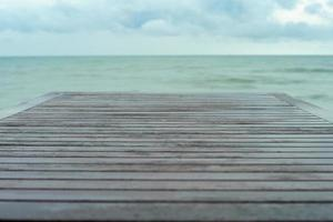 Selective focus on wooden table surface with blurred horizontal line and blue cloudy sky in the background photo