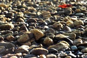 Selective focus on crowds of small rocks on a beach with blurred glittering bokeh light in background photo