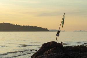 Selective focus on a torn flag on an old bamboo stick located in the rock on the coast photo