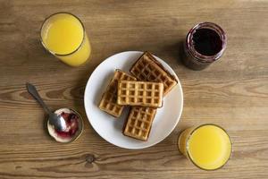 Waffles with orange juice and jam photo