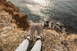 pies de mujer junto a un acantilado cerca del mar foto