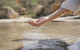 mujer, mojar la mano, en, agua del océano foto