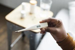 persona que controla su temperatura con un termómetro foto
