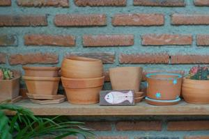 Close up of empty clay pots on the wooden shelf with blurred bricklayer wall background photo