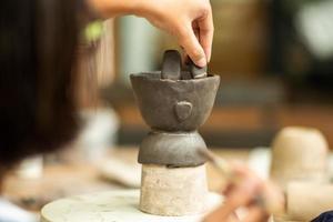 Cerca del trabajo de arcilla con las manos de una niña decorando su trabajo poniendo barro con un primer plano y un fondo borrosos foto
