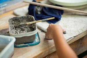 Movimiento borroso de manos de una niña moldeando arcilla con barro húmedo en una bandeja de plástico foto