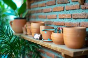 Closeup of empty clay pots on the wooden shelf with bricklayer wall background photo