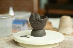 Primer trabajo de arcilla de una cara de conejo con una cinta en la oreja foto
