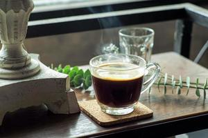 Closeup of a glass of hot black coffee with smoke on a wooden table photo