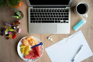 Top view of a laptop on the wooden desk with stationary, coffee, and mixed fruit on a white plate. Work from home. Quarantine at home photo