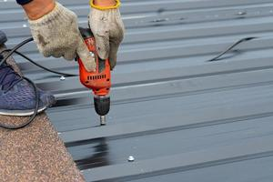 Workers installing a metal sheet roof with an electrical drilling machine. Selective focus on the drilling tool while building the roof photo