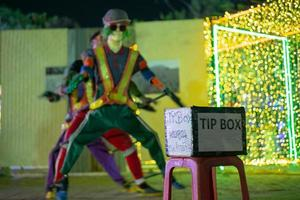 Selective focus on a tip box in front of a dancing performance on a public street. The Thai language means Thank you for the support. photo