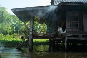 Ratchaburi, Tailandia - 25 de noviembre de 2018 - estilo de vida del pueblo tailandés en una zona urbana. una mujer sentada en su casa de madera cocinando mientras un niño juega con el agua. el memorial del rey rama ix foto